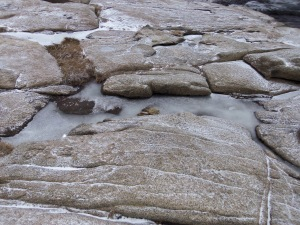 Pools of sea spray are frozen tight in the crevices of boulders overlooking the water.