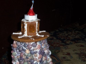 A small electric candle hangs upside down to illuminate the caramelized window panes of the lamp room. A candy kiss provides an improvised cone to top the lighthouse.