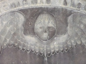 The winged death's head is a common gravestone motif in New England. This example is in Watertown, Massachusetts.