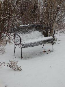 This wrought-iron love seat in a far corner of our yard also serves as a measure of our snowfall. Frequently, the snowpack rises to the seat itself -- and often to the top of the back rail.